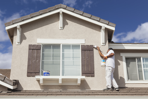 Picture of an employee on the roof of a home painting the shutters in Providence, RI