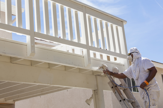 Picture of an employee with a facial mask on spray painting a deck for a home in Providence, RI